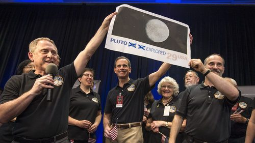 "The 1991 stamp that served as the rallying cry for the New Horizons Mission to Pluto is ""updated"" by members of the New Horizons science team on July 14, 2015, the day the spacecraft reached Pluto. The ""Pluto—Explored!"" stamps issued May 31, 2016, by the U.S. Postal Service set the record straight."